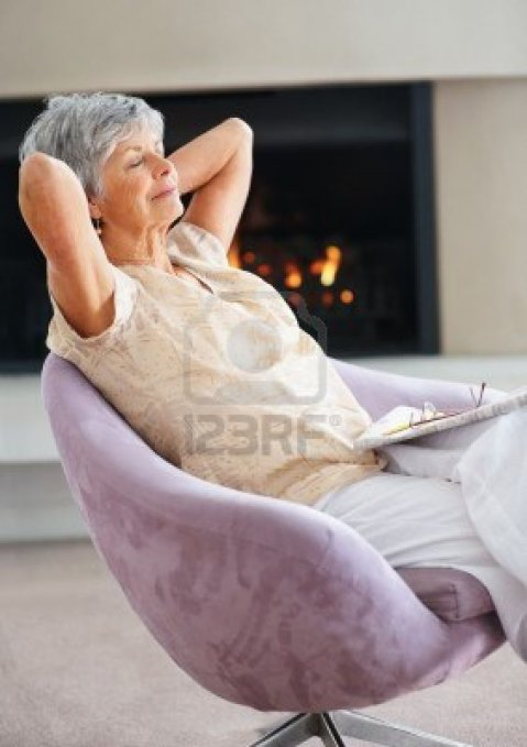 6352018-relaxed-and-retired-elderly-woman-sitting-on-the-chair-by-the-fireplace