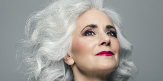 Woman with big grey hair looking up, portrait.