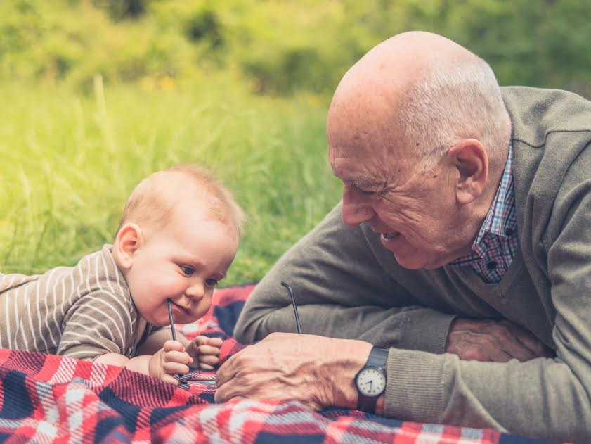 A senior man is playing with his grandchild on a picnic blanket in nature