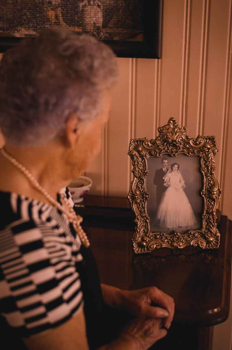 woman standing near photo frame with newly wed couple picture